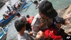 Polisi menggendong seorang anak yang tidak sadarkan diri setelah perahu yang membawa para pencari suaka tenggelam di Cianjur, Jawa Barat. (Foto: Dok)