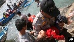 Polisi membawa seorang anak yang pingsan pasca kapal karam di Jawa Barat (24/7).
