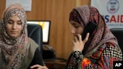 Seorang pengacara Pakistan Shandana Naeem, kanan, sedang menelepon bersama rekannya Nayab Hassan di kantor mereka di Peshawar, 28 Maret 2017. (Foto: AP)
