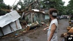 Cư dân bị thương đứng nhìn căn nhà bị hư hại vì bão Koppu ở ngoại ô thành phố Quezon, phía bắc Manila, Philippines, ngày 19/10/2015.