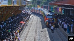 "Sri Lankan ethnic Tamils gather on platforms and welcome the train ""Queen of Jaffna,"" as it arrives at Jaffna, Oct. 13, 2014."