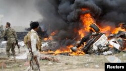 Tentara Syiah yang dikenal dengan sebutan Hashid Shaabi memandangi asap yang mengepul dari kendaraan berpeledak yang dikemudikan pembom bunuh diri ISIS di sebelah selatan Tikrit.
