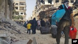26일 시리아 다마스커스 인근 다라야 주민들이 생필품과 옷가지 등을 싸들고 마을을 떠나고 있다.