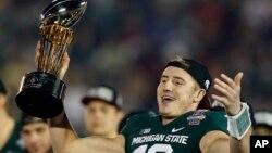 El quarterback de Michigan State, Connor Cook, muestra el trofeo ganado al derrotar a Stanford en el Tazón de las Rosas, en Pasadena.