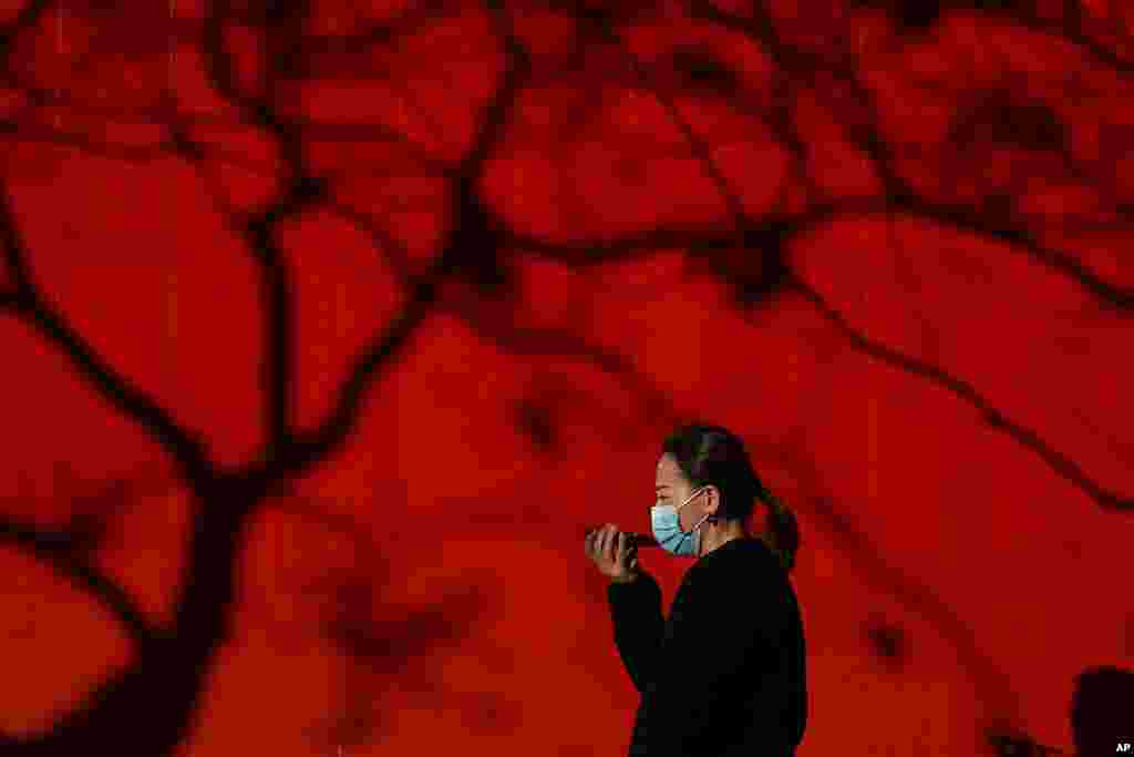 A woman wearing a face mask to help curb the spread of the coronavirus talks on her smartphone as she walks by tree shadow cast on a truck parked on a street in Beijing.