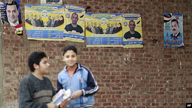 Boys stand near campaign posters of the Muslim Brotherhood's Freedom and Justice Party outside a polling station during the second day of parliamentary elections in the village of Kafr el-Moseilha, the hometown of former president Hosni Mubarak, December