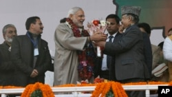 Indian Prime Minister Narendra Modi, center, is given flowers as he arrives for a campaign rally ahead of local elections in Srinagar, in Indian-controlled Kashmir, Dec. 8, 2014.