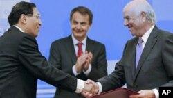 中国开发银行副总裁郑之杰(左)与BBVA银行总裁冈萨雷斯握手
