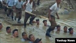 북한 조선중앙TV는 3일 '인민군대를 인민의 행복의 창조자로 이끌어 주시여'라는 제목이 붙은 약 1시간 분량의 새 기록영화을 방영했다. 영상에는 병사 약 15명이 수심 1m가 조금 넘는 작은 개천에 들어가 '인간 다리'를 만드는 모습이 나온다.