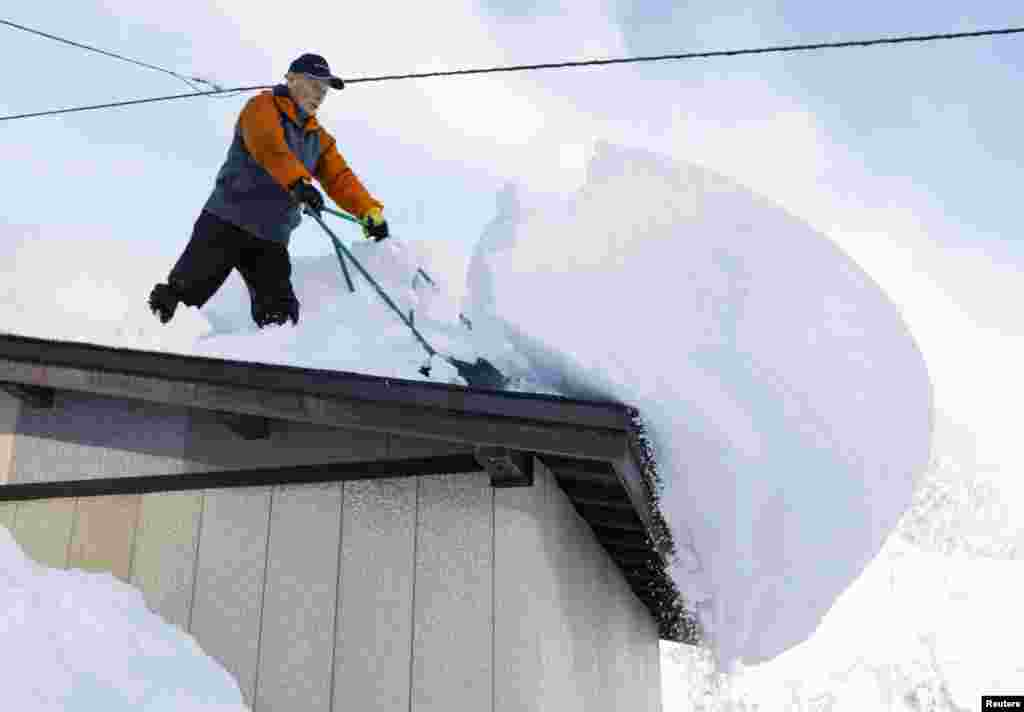 A man clears snow from a rooftop in Oishida, Yamagata Prefecture, Japan, in this photo taken by Kyodo.