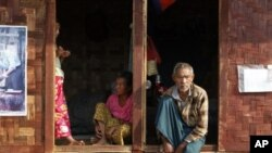Ethnic Kachin people sit in the doorways of shelters at a temporary camp for people displaced by fighting between government troops and the Kachin Independence Army, or KIA, outside the city of Myitkyina in the north of the country, February 22, 2012.