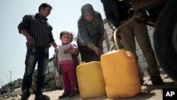 Une famille palestinienne achète de l'eau potable remplit d'eau potable dans le camp de réfugiés de Khan Younes, au sud de la bande de Gaza.