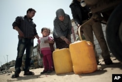 FILE - A Palestinian family fill plastic gallons with drinking water they bought from a vendor in Khan Younis refugee camp, southern Gaza Strip.