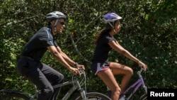 Presiden AS Barack Obama bersepeda besama anaknya Malia ketika berlibur di kebun anggur Martha di Massachusetts, 15 Agustus 2014.
