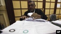 开罗的投票站周六关闭后,一位官员在检查选票