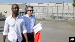 FILE - Rudy Guede, left, is greeted by an unidentified person as he leaves the Viterbo's penitentiary, Italy.