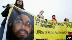 FILE - Human rights activists hold a banner with a picture of Shaker Aamer. The last British resident of the U.S. prison in Guantanamo Bay in Cuba has been released.