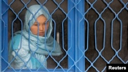 Một tù nhân theo dõi sự kiện truyền thông đằng sau chấn song, tại một nhà giam phụ nữ ở Kabul