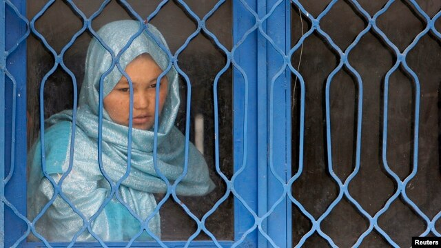 An Afghan inmate watches from behind a barred window during a media event at a women's prison in Kabul, March 30, 2010.