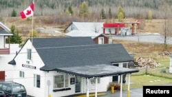 FILE - Ouellete's Gaz Bar, background, sits in Estcourt Station, Maine, 150 feet from the U.S. border with Canada at the town of Pohenegamook, Quebec.
