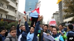 FILE - Iranian schoolboys chant slogans while holding an effigy of U.S. President Donald Trump in an annual gathering in front of the former U.S. Embassy marking the anniversary of its 1979 takeover, in Tehran, Iran, Nov. 4, 2017.