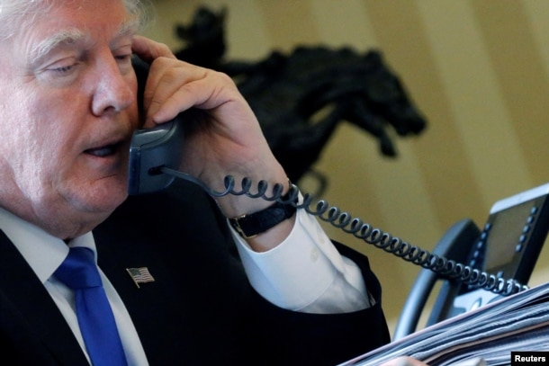 U.S. President Donald Trump speaks by phone with Russia's President Vladimir Putin in the Oval Office at the White House in Washington, Jan. 28, 2017.