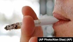 In this photo taken Monday, Feb. 7, 2011, a person smoking a Marlboro cigarette.