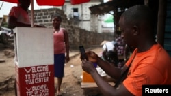 FILE - A man checks out a mobile phone at a kiosk in Sierra Leone's capital, Freetown. The administration on Thursday sharply denied reports that it planned to gag citizens from freely expressing their views on social media platforms.