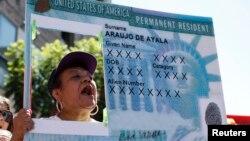 Seorang perempuan menunjukkan replika green card atau kartu hijau dalam unjuk rasa menuntut reformasi imigrasi di Hollywood, Los Angeles, California, 5 Oktober 2013.