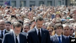 King Felipe of Spain, center, Prime Minister Mariano Rajoy, center left, and Catalonia regional President Carles Puigdemont, center right, join people gathered for a minute of silence in memory of the terrorist attacks victims in Barcelona, Spain.