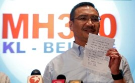 Malaysia's acting Transport Minister Hishammuddin Hussein holds up a note that he has just received on a new lead in the search for the missing Malaysia Airlines Flight MH370, during a news conference at Kuala Lumpur International Airport, Mar. 22, 2014.