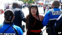 Police in Santa Fe, N.M., lead away protest organizer Jennifer Marley of San Ildefonso Pueblo in hand restraints, Sept. 8, 2017. Police say they arrested at least 12 people to contain protest against an annual pageant marking the return of Spanish conquistador Don Diego de Vargas to New Mexico following a 17th century Indian revolt.