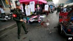 Seorang polisiberdiri di dekat lokasi ledakan di pusat lokasi demo anti-pemerintah di Bangkok, Thailand (23/2).
