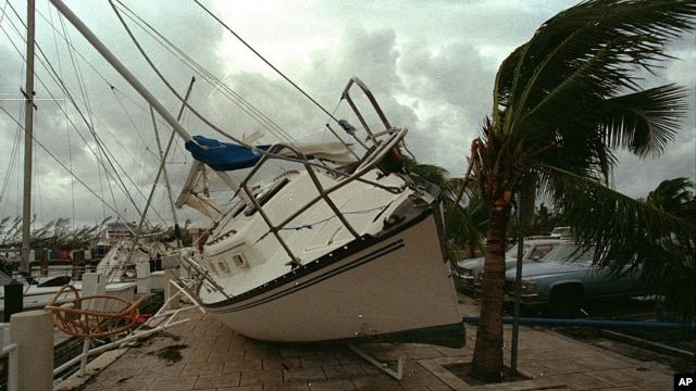 In this Aug. 24, 1992 photo, a sailboat sits on a sidewalk at Dinner Key in Miami after it was washed ashore by Hurricane Andrew.