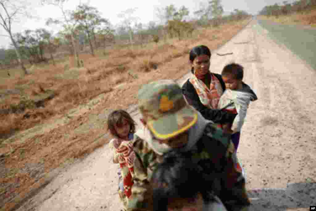 A Cambodian family is seen on an empty road as they flee the area near the 11th-century Preah Vihear temple at the border between Thailand and Cambodia February 7, 2011. Thai and Cambodian troops clashed for a fourth straight day on Monday over a disputed