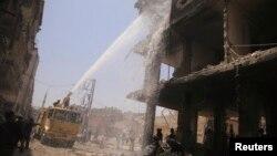 Dân phòng cố gắng dập tắt đám cháy sau vụ nổ bom xe hơi ở Douma, 28/6/2014.