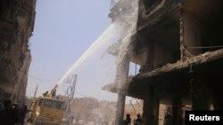 مأموران آتش نشانی در تلاش برای خاموش کردن حریق ناشی از انفجار بمب در بازاری در حومه دمشق - دوما، ۲۸ ژوئن ۲۰۱۴