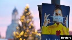 "Poster bertuliskan ""Aku melindungimu"" saat dimulainya pengetatan restriksi untuk mengurangi penyebaran virus Covid-19 di Dresden, Jerman, 14 Desember 2020. REUTERS / Matthias Rietschel"