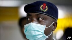 FILE - A Nigerian health official wearing a protective mask waits to screen passengers at the arrivals hall of Murtala Muhammed International Airport in Lagos, Nigeria.