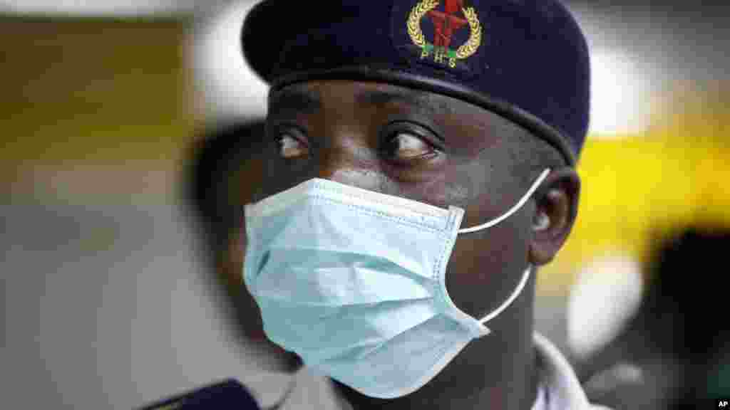 A Nigerian health official wearing a protective mask waits to screen passengers at the arrivals hall of Murtala Muhammed International Airport in Lagos.