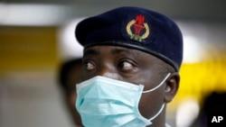 Seorang petugas kesehatan Nigeria mengenakan masker pelindung menunggu penumpang yang tiba di Bandara Internasional Murtala Muhammed di Lagos, Nigeria, Senin, 4 Agustus 2014.