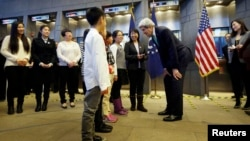 U.S. Secretary of State John Kerry (3rd R) chats with one of Chinese teacher Peng Ye (4th R)'s four students during an issuance ceremony to be the first Chinese citizens to receive ten-year U.S. visas from Kerry at the U.S. embassy, in Beijing, November 1