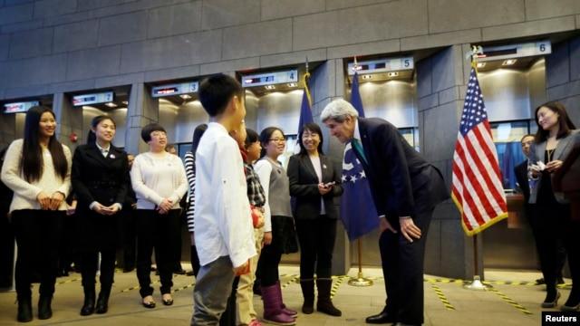 Ngoại trưởng Hoa Kỳ John Kerry (thứ ba từ phải sang) trò chuyện với một trong bốn em học sinh trong buổi lễ trở thành những công dân Trung Quốc đầu tiên được cấp visa Mỹ 10 năm tại đại sứ quán Hoa Kỳ ở Bắc Kinh, 12/11/2014.