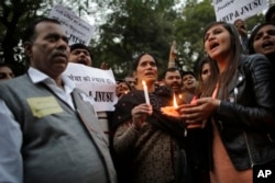 FILE - The father, left and mother, center, of the Indian student victim who was fatally gang raped on this day three years ago on a moving bus in the Indian capital, join others at a candle lit vigil in New Delhi, India, Dec. 16, 2015.