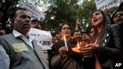 The father, left and mother, center, of the Indian student victim who was fatally gang raped on this day three years ago on a moving bus in the Indian capital, join others at a candle lit vigil in New Delhi, India, Dec. 16, 2015.