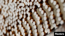 FILE - Cigarettes are seen during the manufacturing process in the British American Tobacco Cigarette Factory (BAT) in Bayreuth, southern Germany. Japan's health minister has said the government is eager to stamp out smoking in public by the time the capital hosts the Olympics.