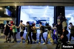 香港理工大学的抗议学生在警察的押送下离开校园。(2019年11月18日)