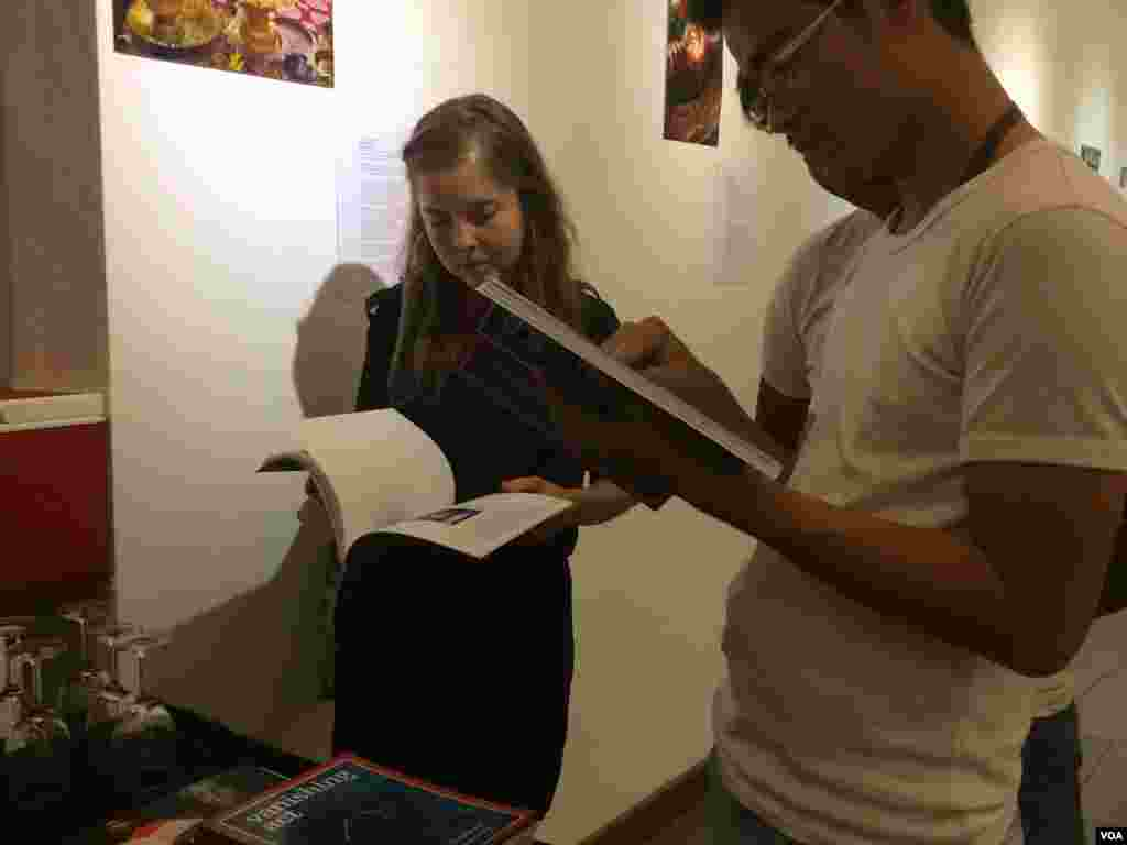 Visitors skim through the 'Vanishing Act' at the book launch Thursday.