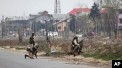 سری نگر میں بدھ کو ہونے والی جھڑپ کے دوران میں بھارتی فوجی اہلکار پوزیشن لے رہے ہیں