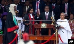 FILE - Kenyan President Uhuru Kenyatta, center, is sworn-in accompanied by his wife Margaret, right, and during his inauguration ceremony at Kasarani stadium in Nairobi, Kenya, Nov. 28, 2017.